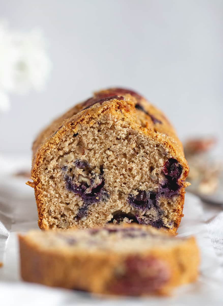 Cut Loaf of blueberry applesauce cake, blurred slice in front