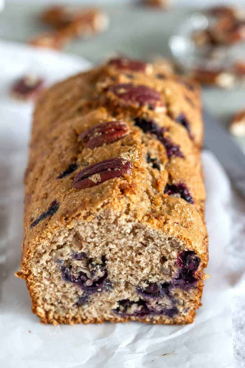 Pecan studded blueberry loaf cake, white surface, scattered pecans