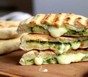 Stack of three filled grilled Naan Breads, oozing cheese on wooden board