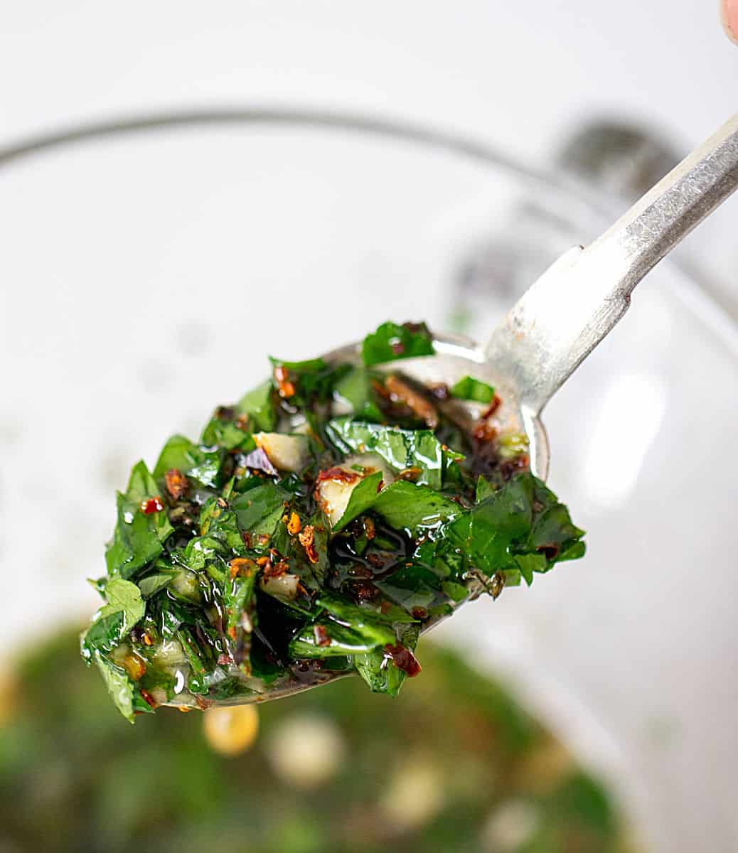 Spoon with chimichurri sauce over glass jar