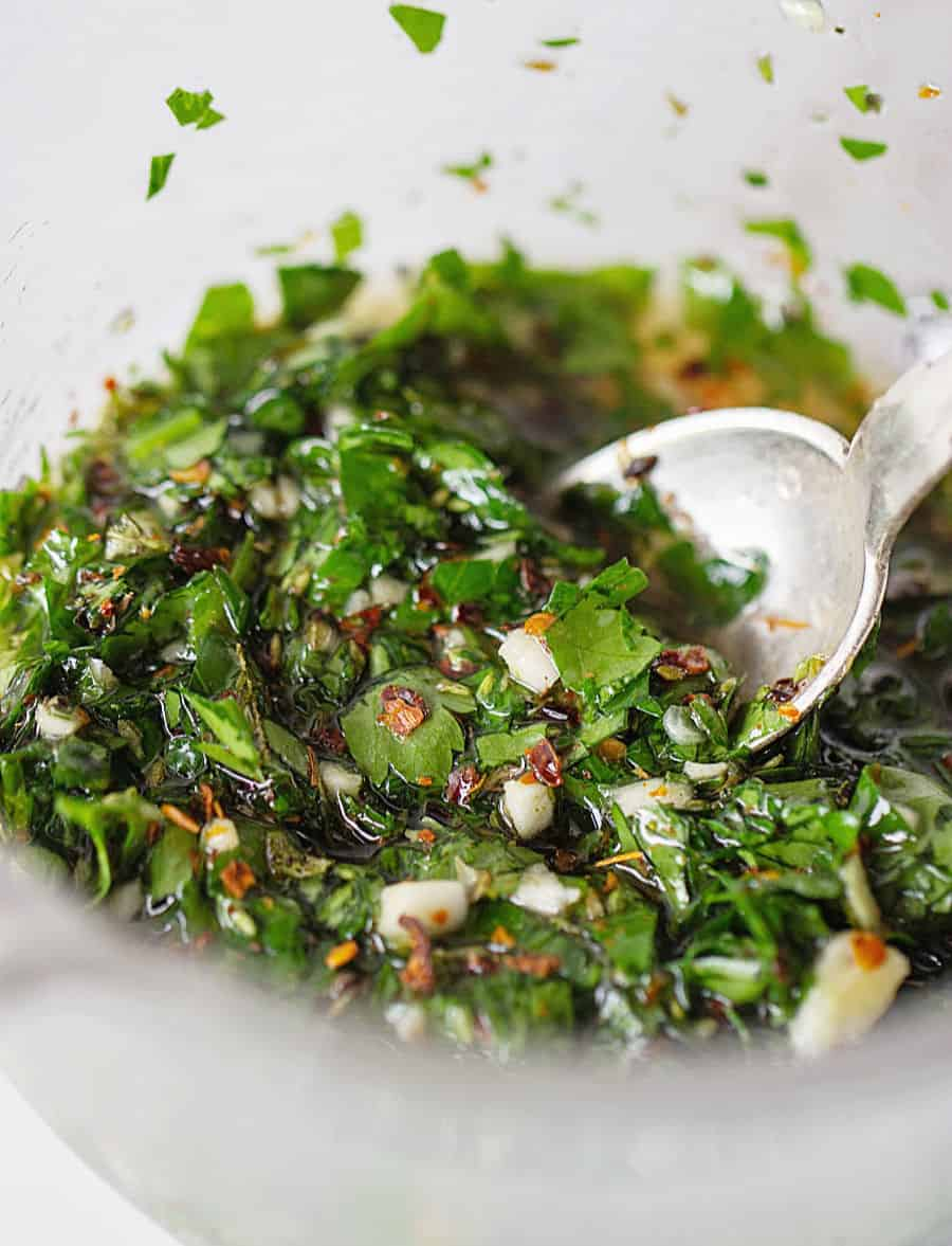 Spooning chimichurri sauce, close up image