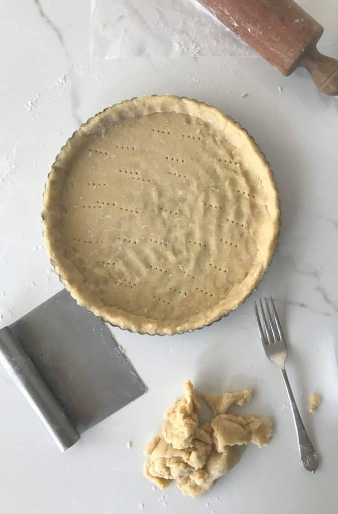 Pie pan lined with sweet dough, fork, cornet, white surface