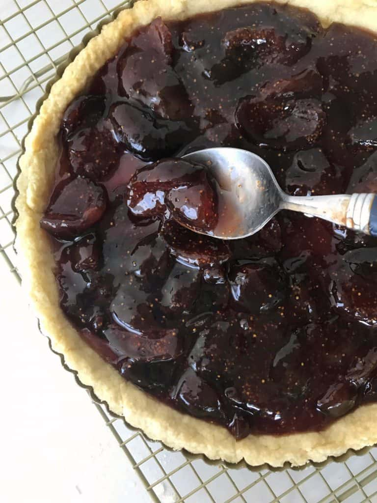 Pie with homemade fig jam on wire rack, spoon