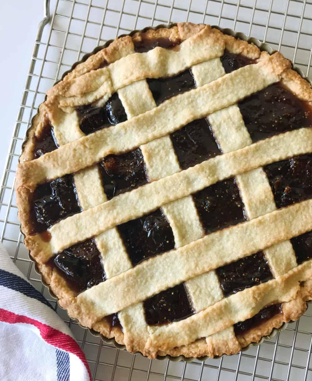 Whole fig lattice tart on wire rack, kitchen towel