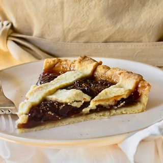 Close up of white plate with slice of lattice fig tart, fork