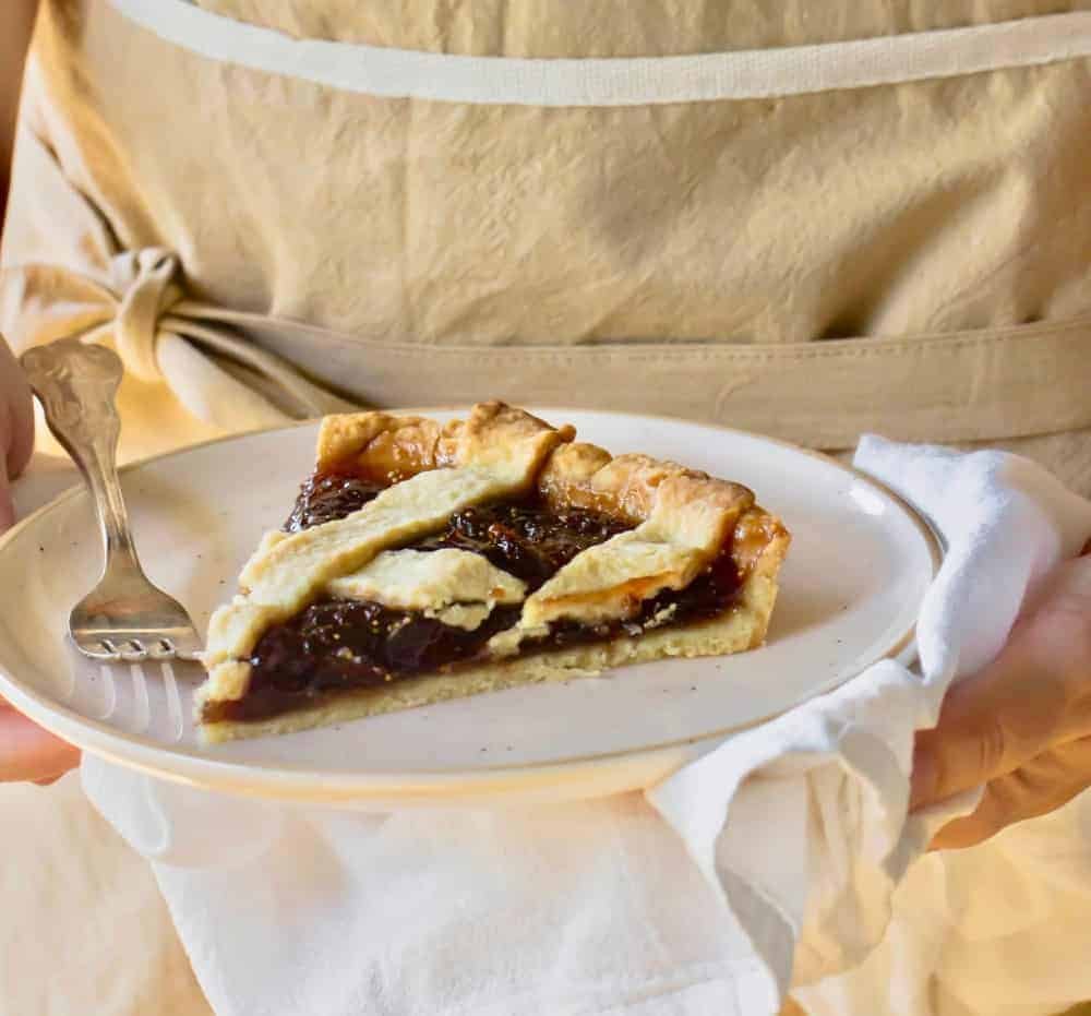 Hands holding white plate with slice of lattice fig tart, fork, white kitchen towel