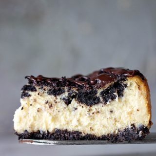 Slice of creamy Oreo Cheesecake on a cake server, grey background