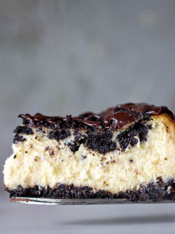 Slice of creamy Oreo Cheesecake on a cake server, grey background