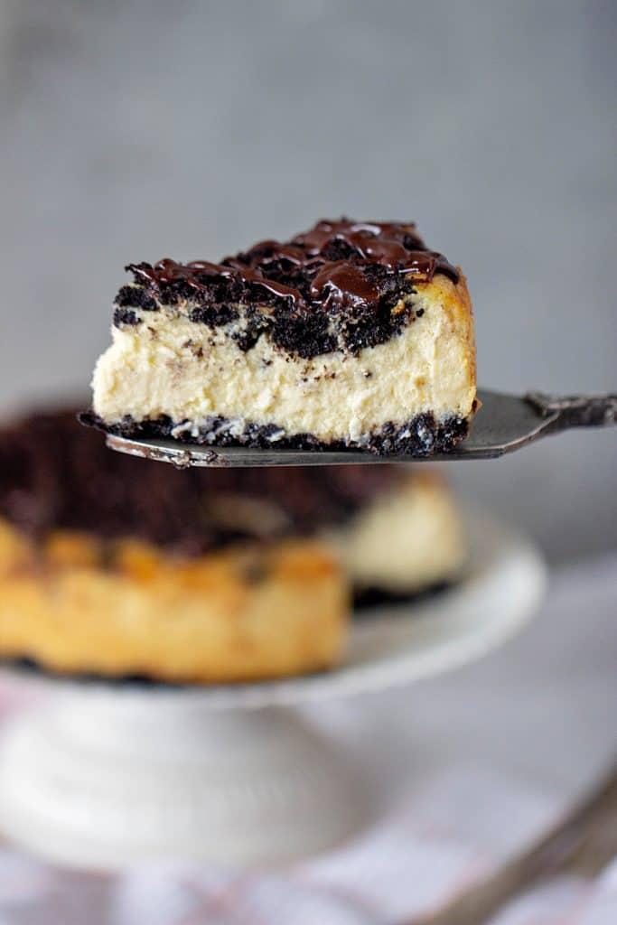 Slice of Oreo Cheesecake on cake server, cake on stand, grey background