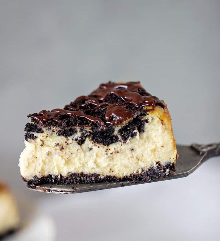 Slice of Oreo Cheesecake on cake server, grey background