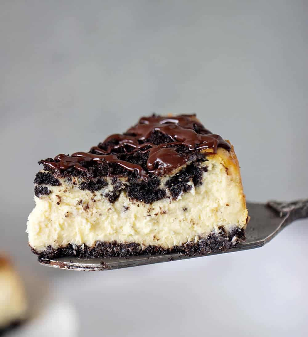Slice of Oreo Cheesecake with chocolate topping on cake server, grey background