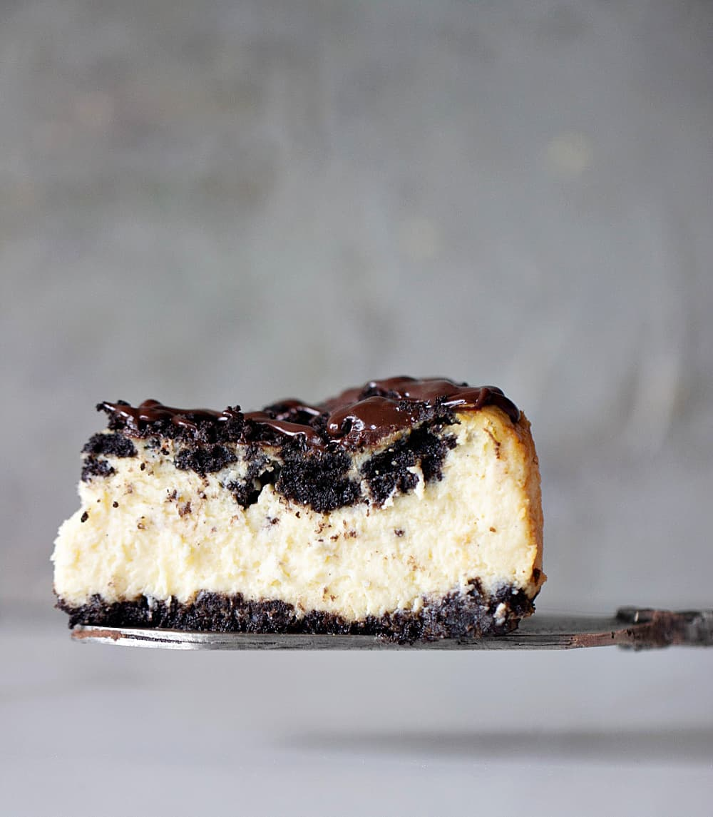 Single slice of Oreo Cheesecake on silver cake server, grey backdrop