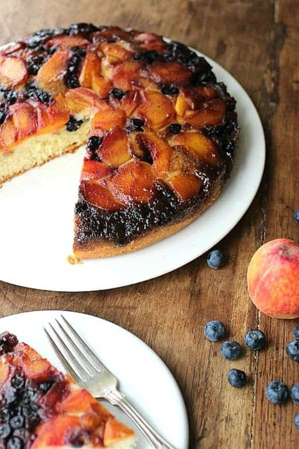 Cut peach blueberry upside down cake on white plate, wooden table, peach and berries, fork