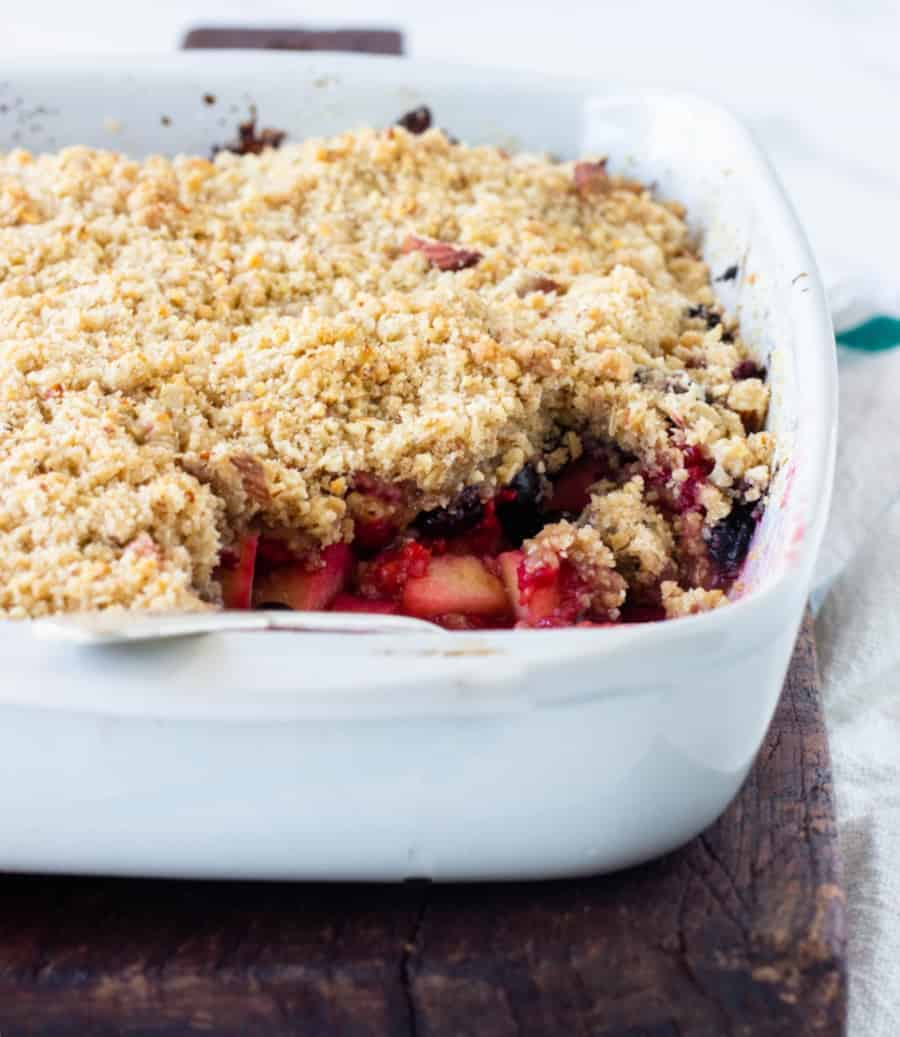 Close-up of white dish with apple berry crumble, spoon, wooden board