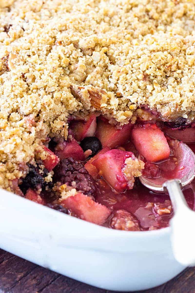 Partial close-up view of silver spoon inside eaten apple berry crumble dish
