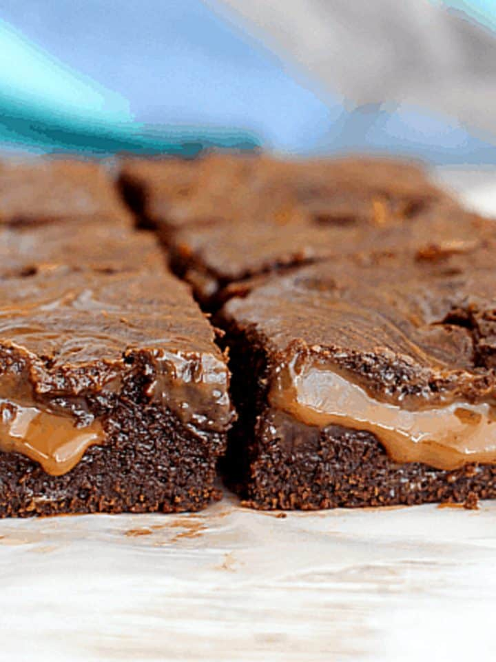 Squares of brownies filled with soft dulce de leche on white surface and bluish background