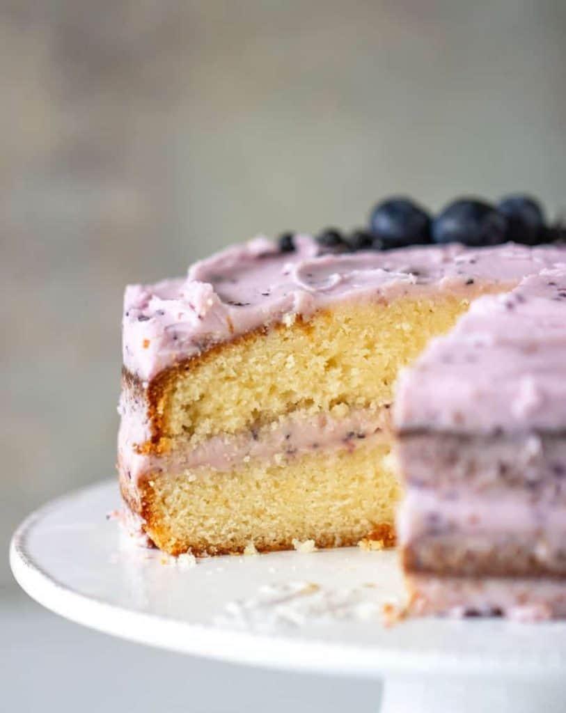 Cut lemon blueberry cake on white cake stand
