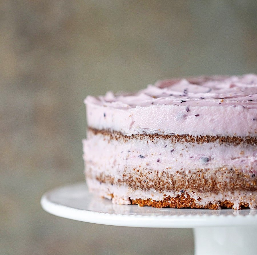 Partial view of frosted lemon blueberry cake on cake stand
