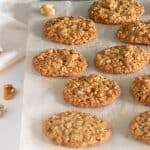 Single layer of oatmeal cookies on parchment paper, white table, loose walnuts