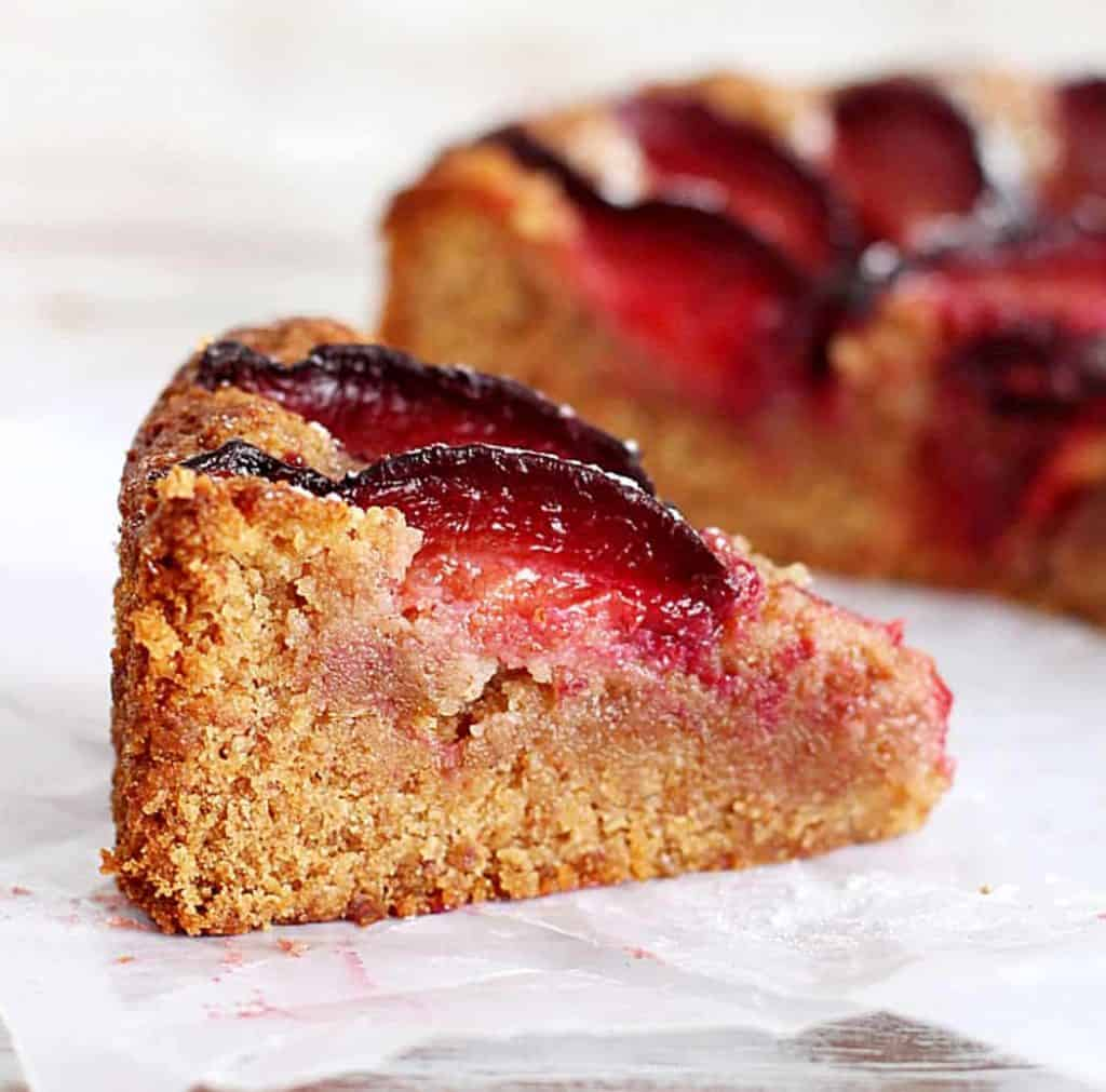 Close-up of almond plum cake on white parchment paper