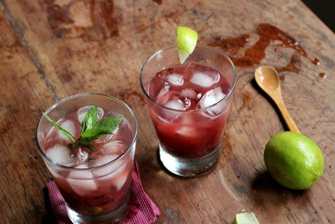 Two glasses of Cherry Caipiroska, a lime, wooden table