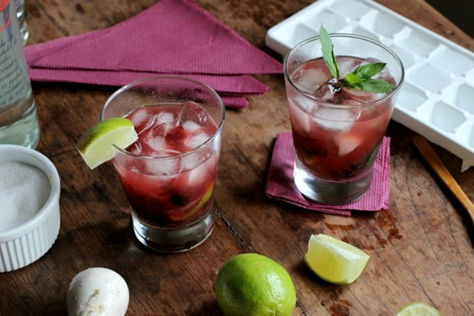 Two glasses of cherry caipiroska on wooden table, ice, purple napkins, lime wedges