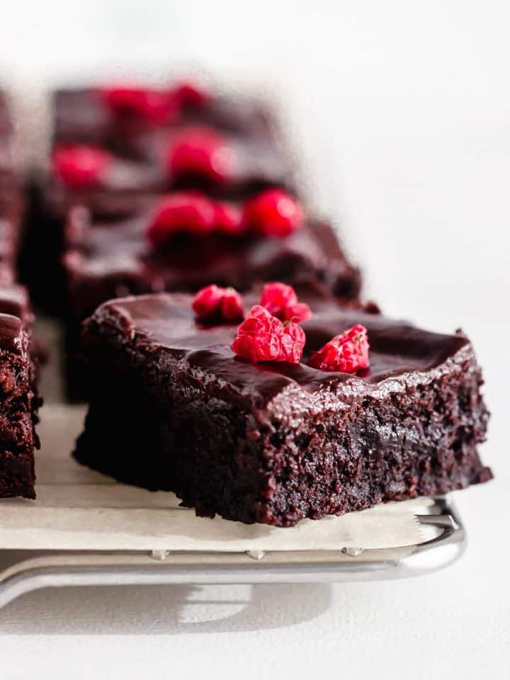 Squares of cocoa brownies, raspberry pieces, wire rack, white surface