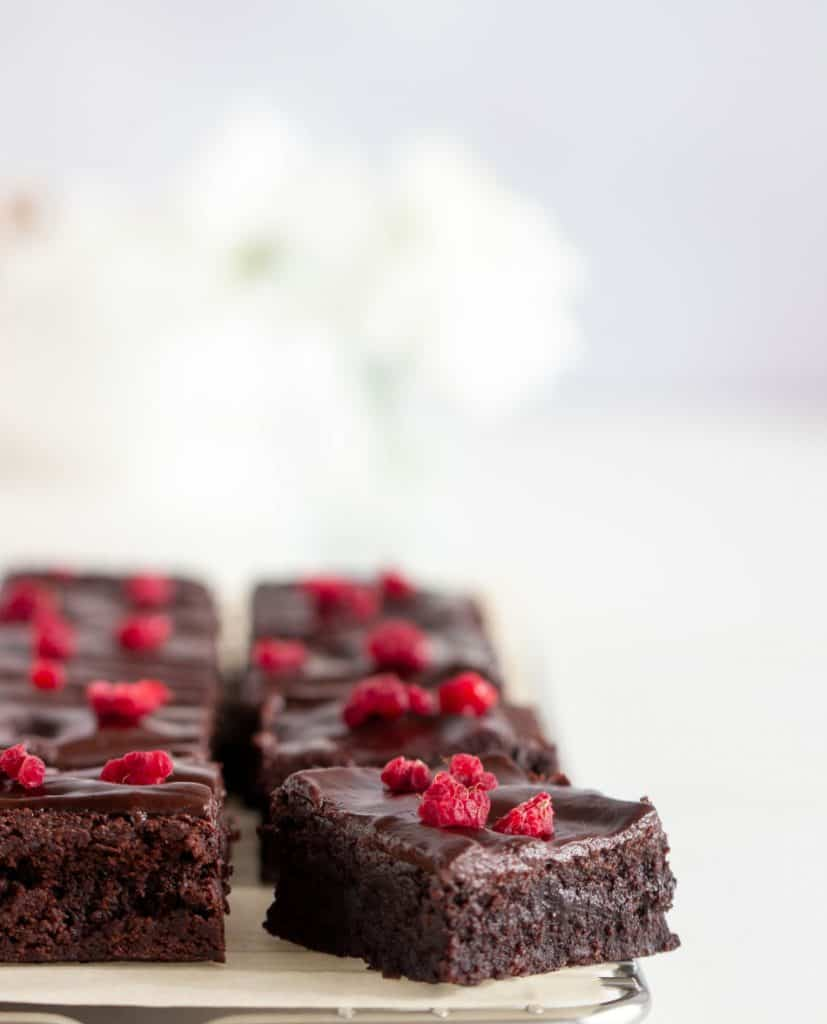 Squares of cocoa brownies, raspberry pieces, white surface
