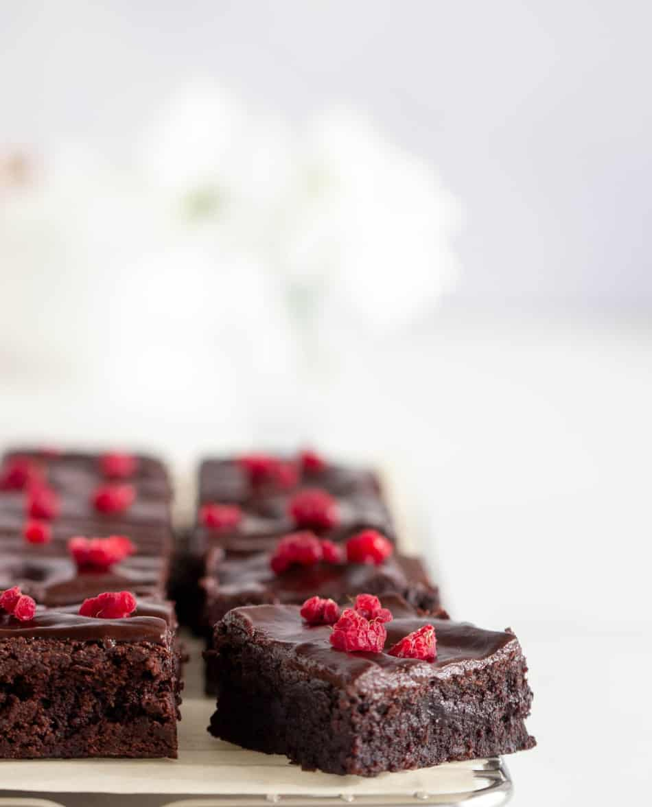 Brownie squares topped with raspberry pieces on wire rack, light colored background