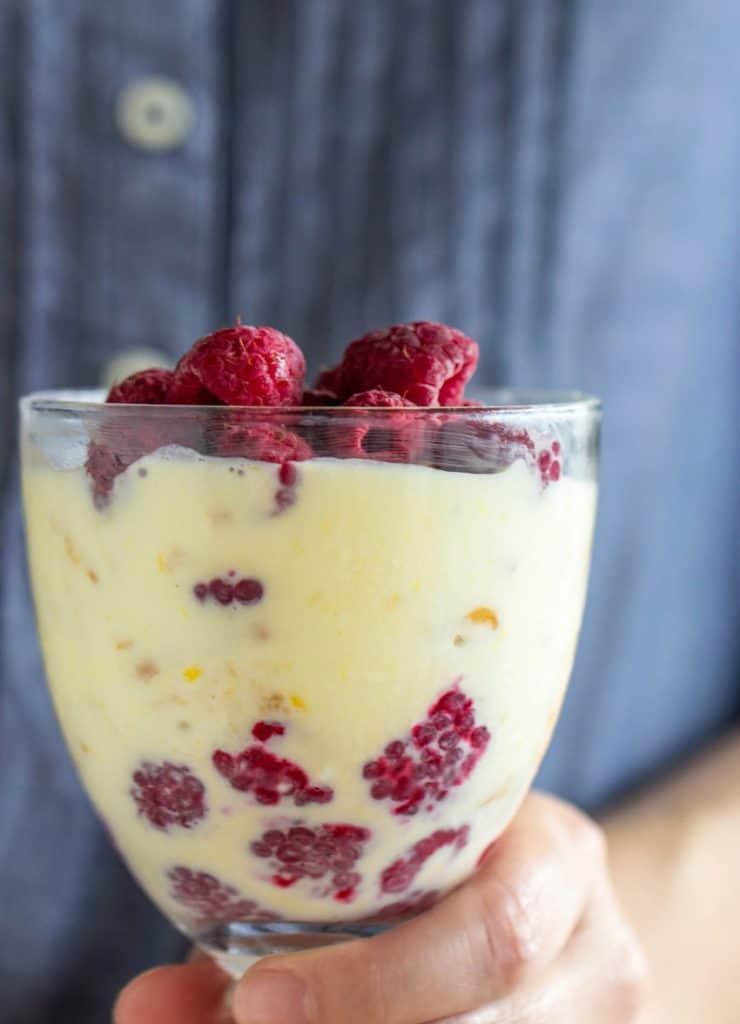 Hand holding glass with lemon raspberry dessert, blue shirt