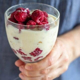 Hand holding glass of lemon raspberry dessert, blue shirt