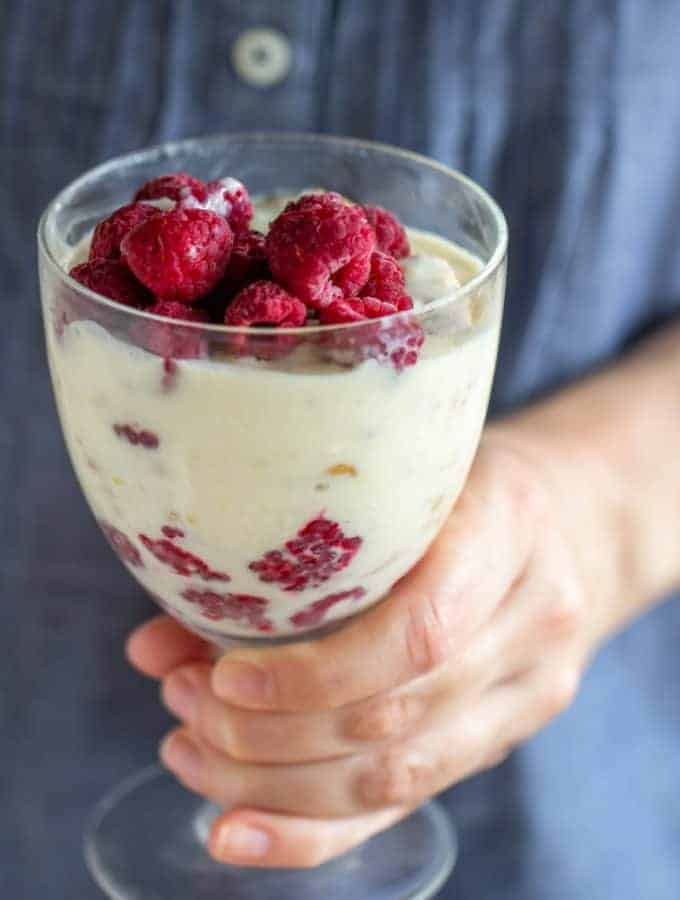 Hand holding glass of lemon raspberry dessert, blue shirt