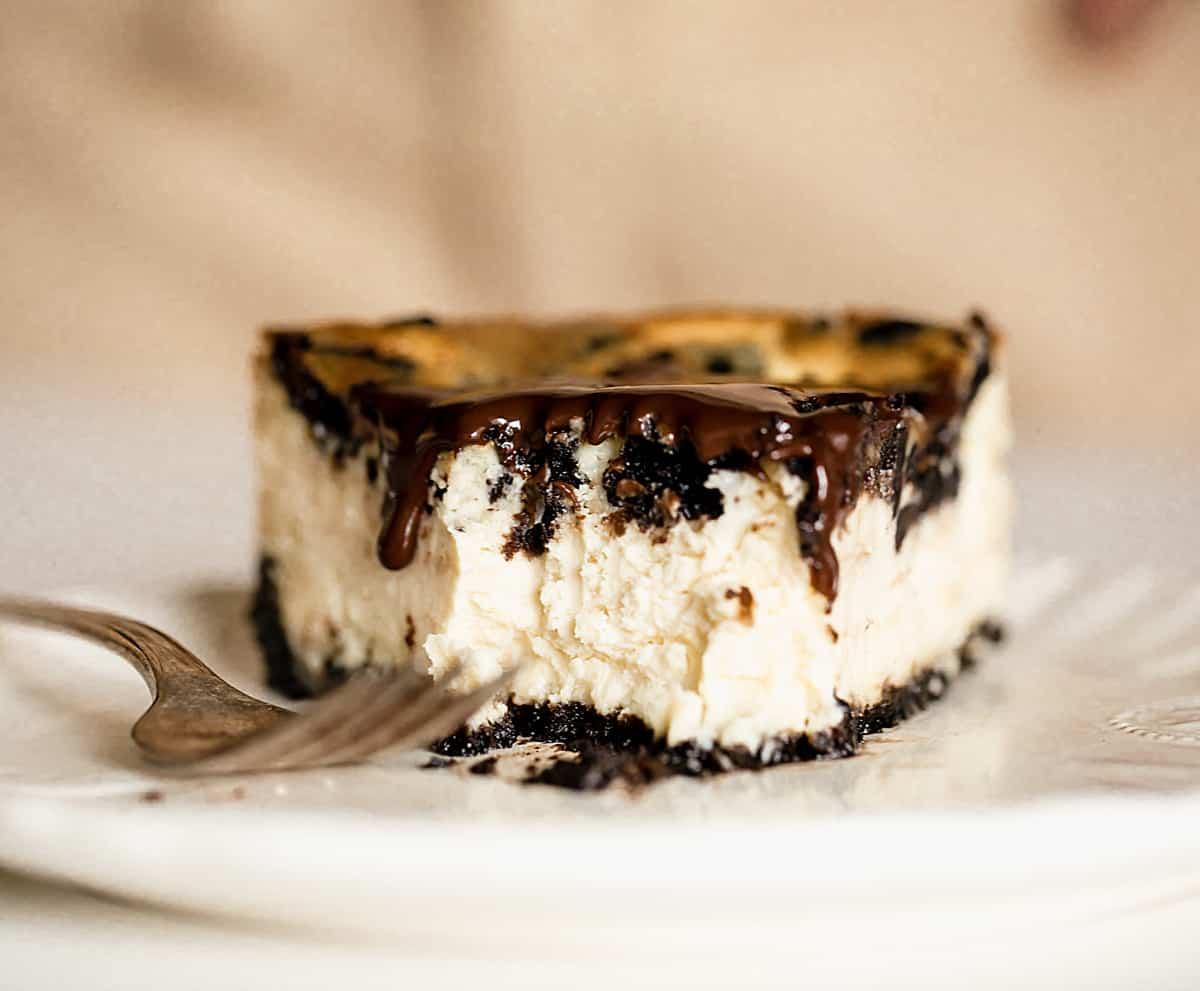 Bitten piece of oreo cheesecake on white plate with fork, beige background