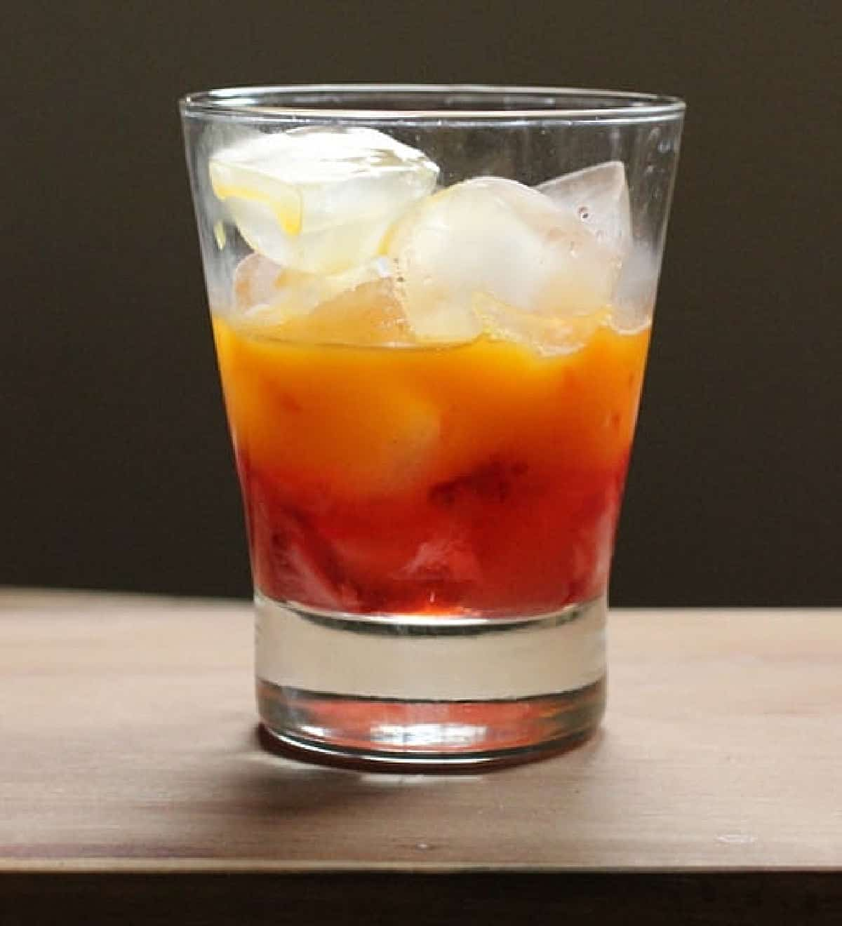 Half filled glass with ice and orange colored drink on wooden board