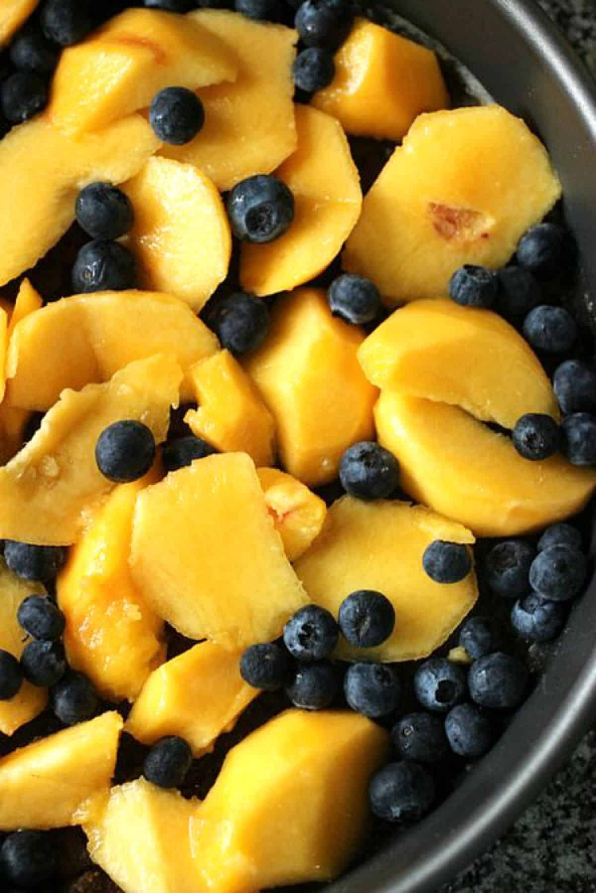 Peach slices and blueberries in round metal pan