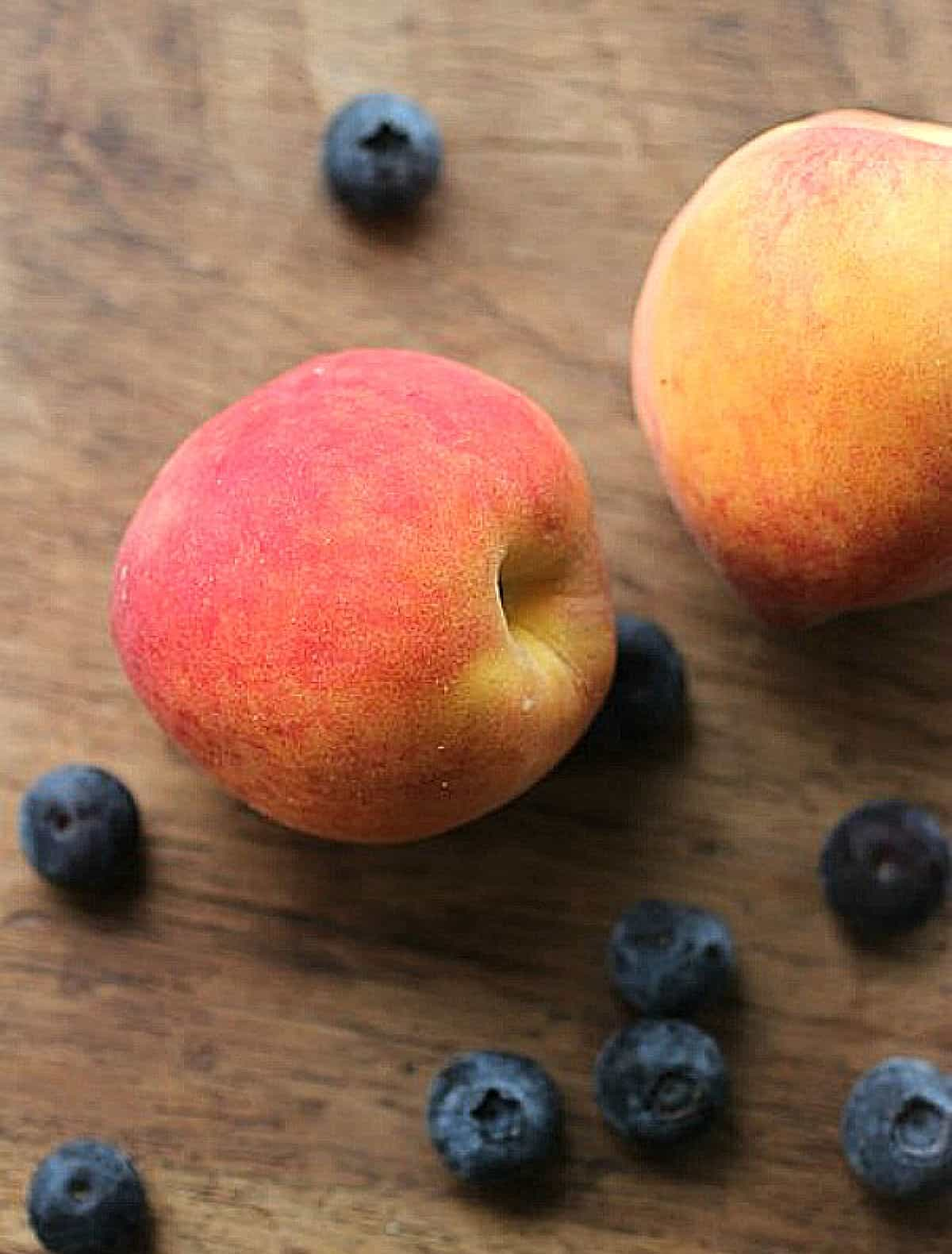 Peaches and blueberries on wooden table