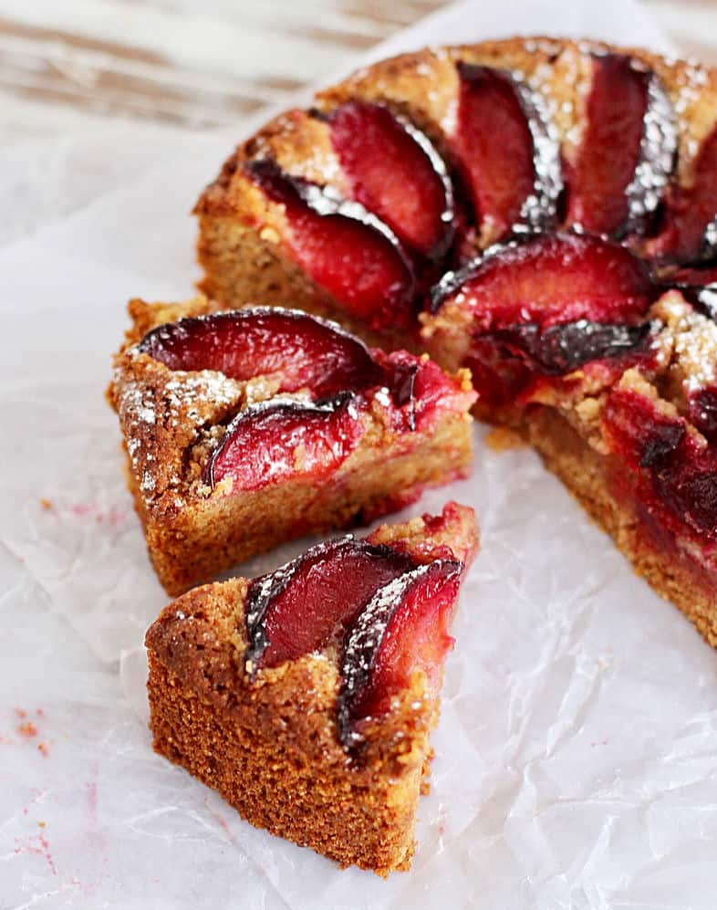 Half cut and slices of plum almond cake on white parchment paper