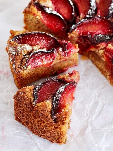Half cake and slices of plum cake on white parchment paper