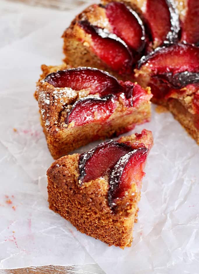Slices of plum cake on white parchment paper