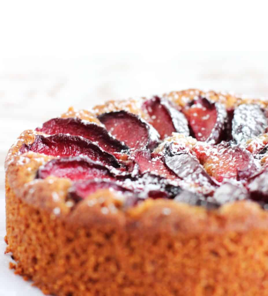 Whole almond plum cake on white surface