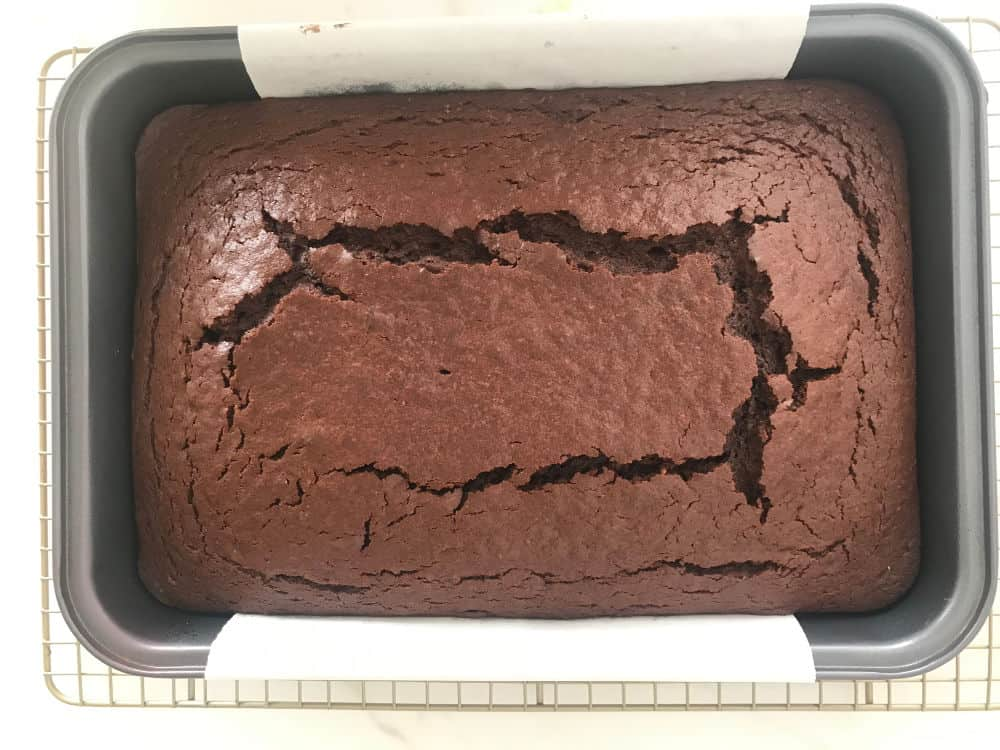 Just baked chocolate cake on metal pan with parchment paper