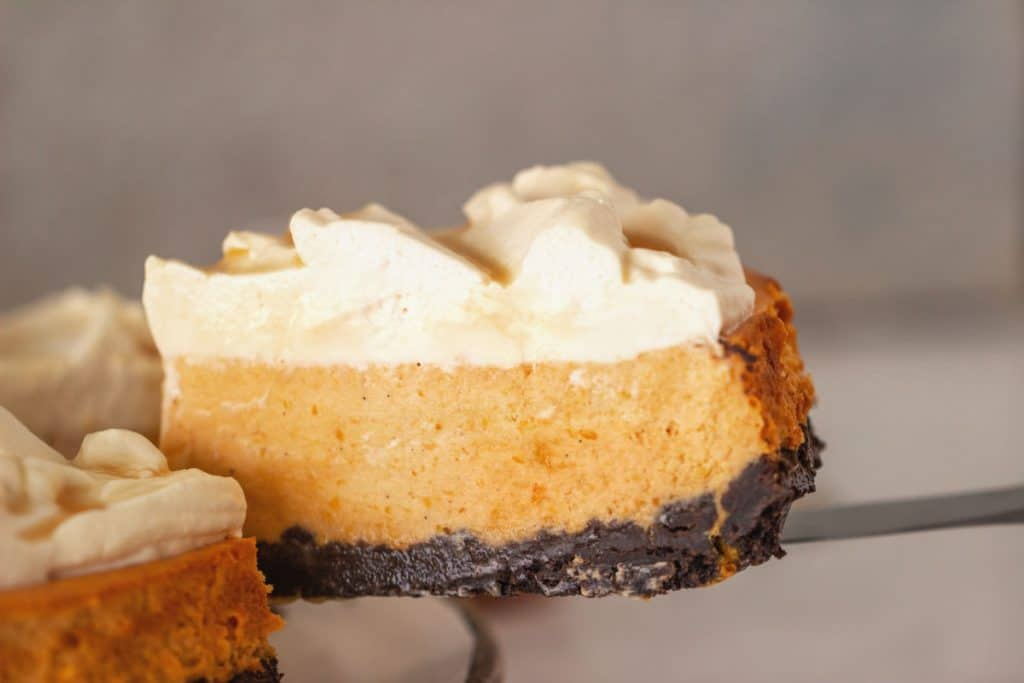 Slice of cream topped pumpkin cheesecake on cake server