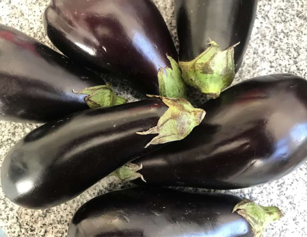 Bunch of dark whole Italian eggplants on grey surface