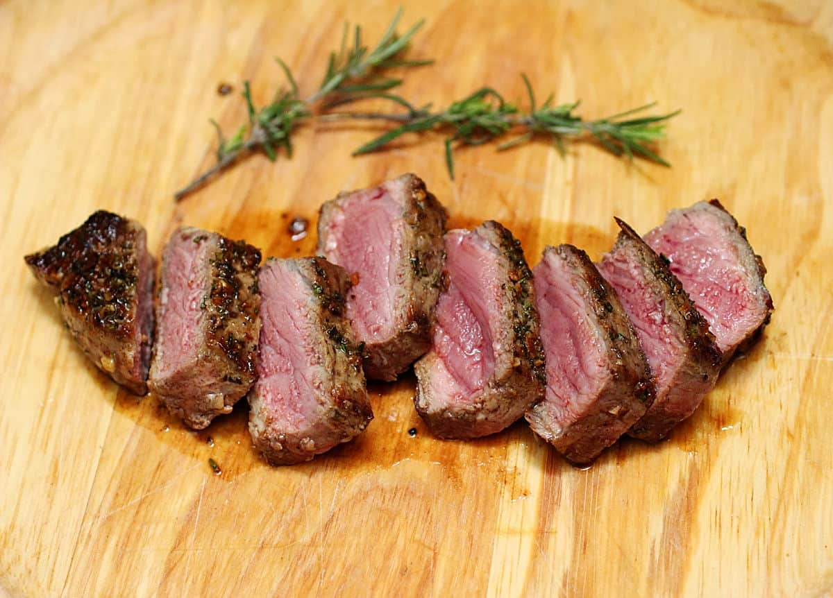 Just sliced steak with pink interior on a light wooden board, rosemary sprigs