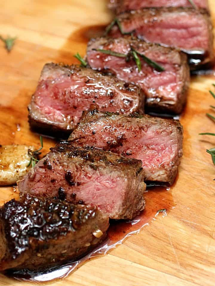 Several cut slices of juicy Rosemary Garlic Butter Steak on wooden board
