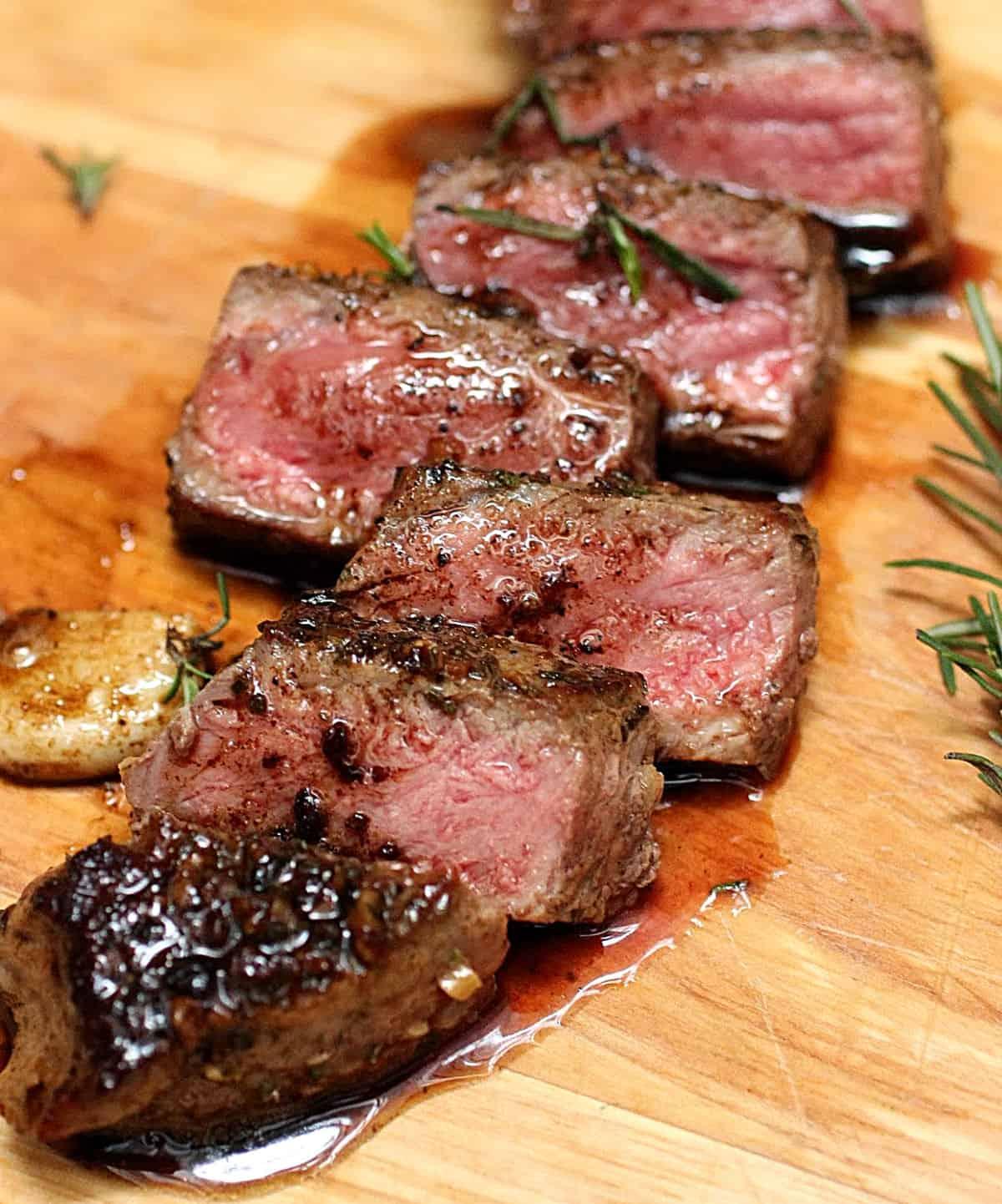 Juicy sliced rump steak on a wooden board, garlic and rosemary around