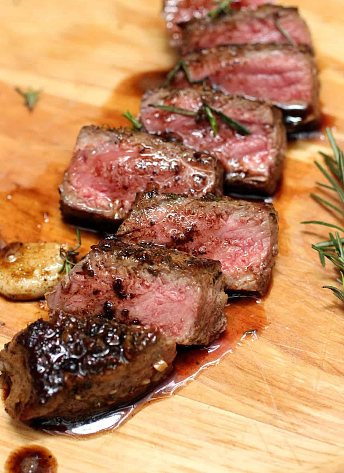 Cut pieces of juicy Rosemary Garlic Butter Steak on wooden board