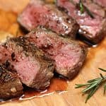 Very close up view of juicy slices of rosemary steak on a wood board