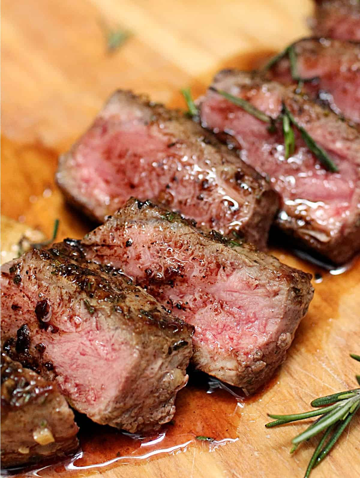 Close up of slices of juicy steak on wooden board, rosemary sprigs