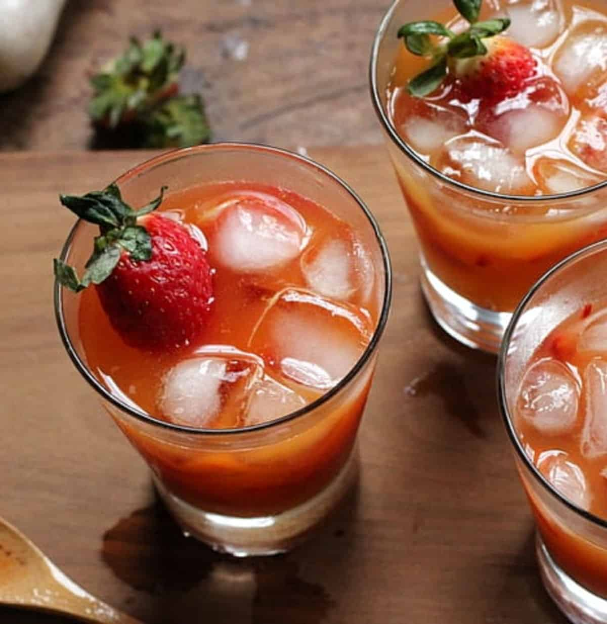 Top view of several glasses with strawberry drink on wooden board
